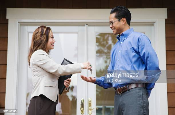 Female real estate agent handing keys to Asian man in front of house