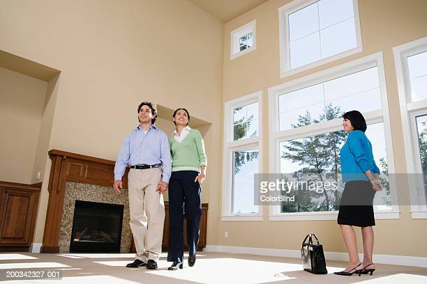 Female real estate agent showing home to young couple