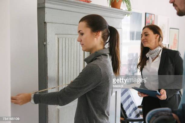 Female realtor and man looking at woman measuring with tape at home