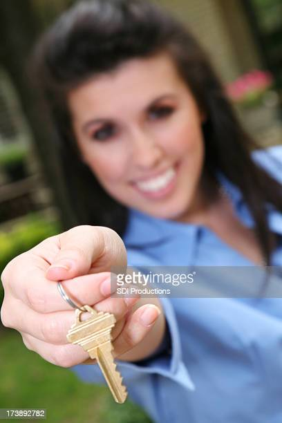 Female Realtor Offering Key in front of New House