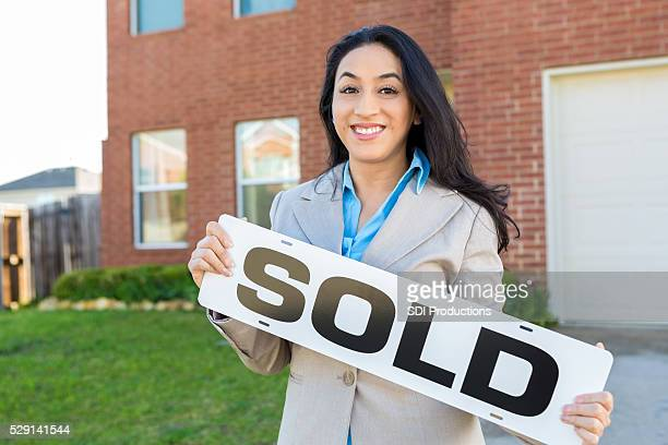 Female realtor or homeowner in front of new home