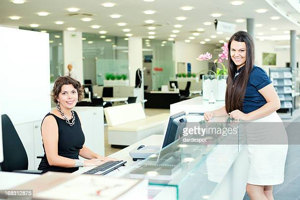 Female receptionist and business woman at reception