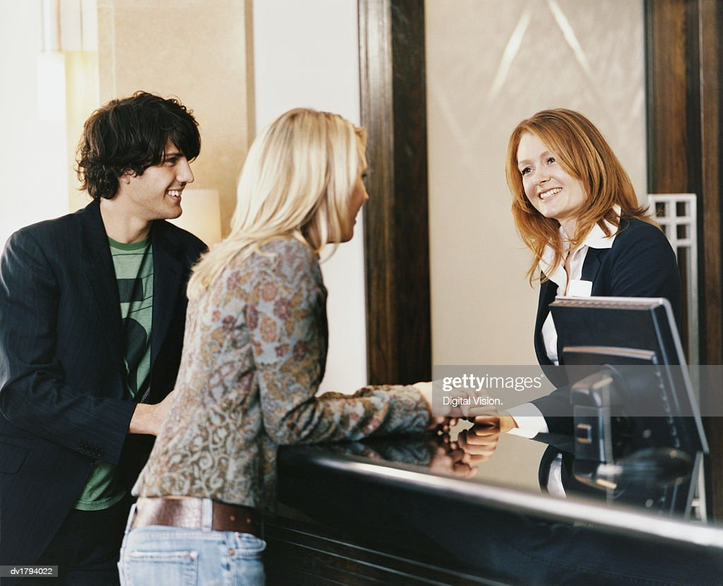 Female Receptionist at a Reception Desk Welcomes a Young Couple to the Hotel : Stock Photo