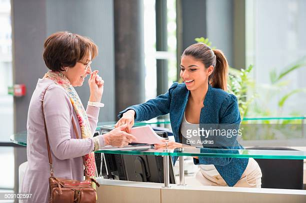 Female receptionist handing papers to a woman at reception desk