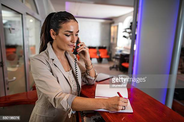 Female receptionist making appointment over the phone.