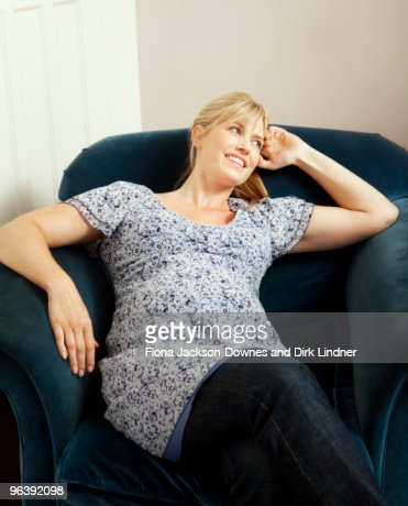 Female relaxing in an arm chair : Stock Photo