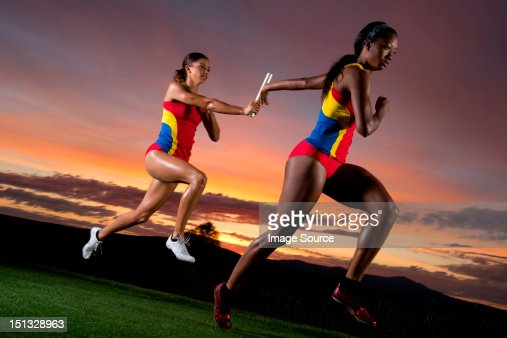 Female relay racers passing baton : Stock Photo
