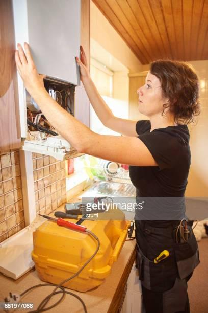 female repairing a boiler
