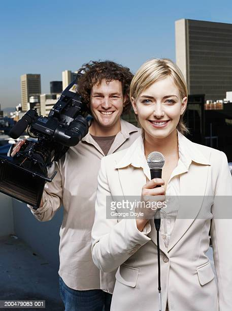 Female reporter and cameraman on balcony, smiling, portrait