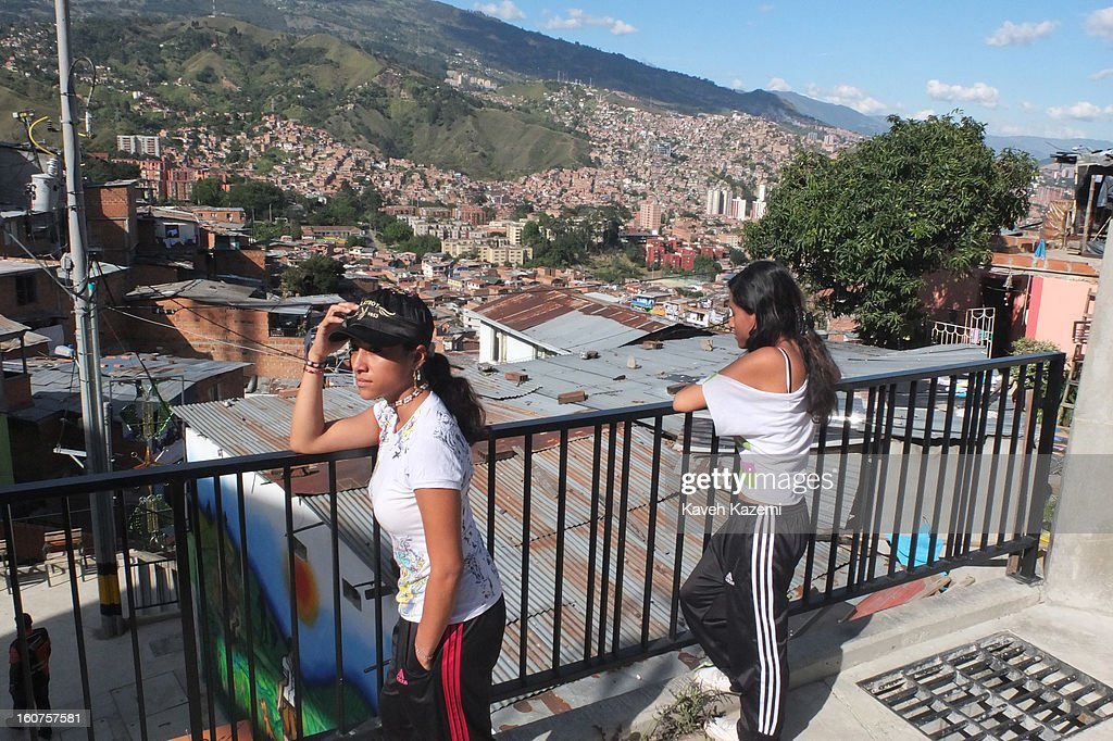 Female residents stand on a terrace overlooking the escalators in '20 de Julio' neighborhood in the Comuna 13 slums on January 5, 2013 in Medellin, Colombia. The stairway is divided into six sections and has a length of 1,260 feet. An escalator goes up and a second goes down.Residents used to climb hundreds of steps to get home from the bottom of the hill, but the journey now takes just 6 minutes. Comuna 13 is the most notorious slums of Medellin with violence occurring everyday.