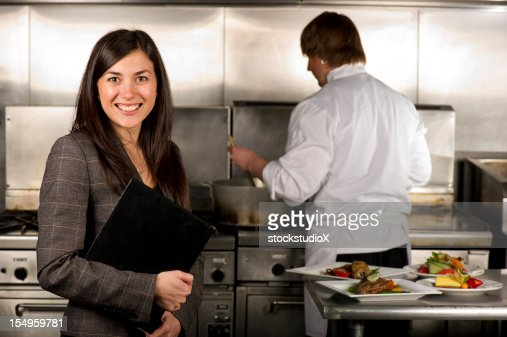 Restaurant Kitchen Manager happy waitress receiving food from chef in commercial restaurant