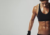 Close up image of middle eastern female in sports clothing relaxing after workout on grey background. Muscular female body with sweat. Image with copyspace for text