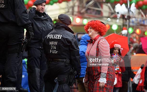 A female reveller walks beside Policemen during Weiberfastnacht celebrations as part of the carnival season on February 4 2016 in Cologne Germany...