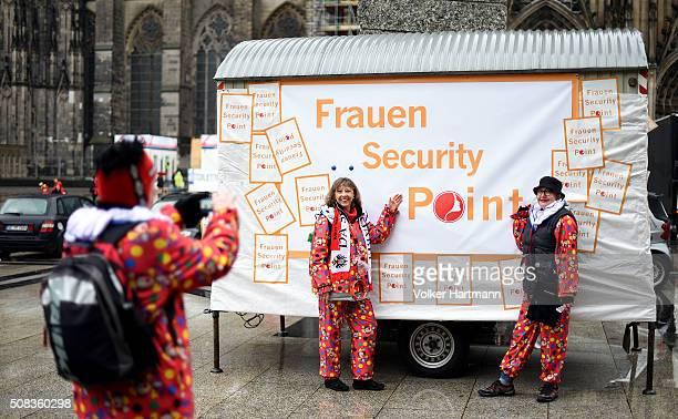 Female revellers take pictures at a 'Frauen Security Point' called Vehicle during Weiberfastnacht celebrations as part of the carnival season on...