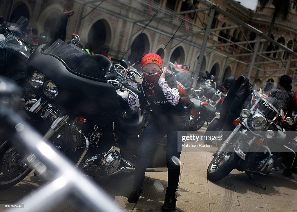 A female rider adjusts her head scarf during the bike parade in the heart of the city on September 16, 2013 in Kuala Lumpur, Malaysia. Malaysia hosts Asia Harley Days, a first of its kind event in Southeast Asia to engage with not only its consumers, but also with their fans in the region.