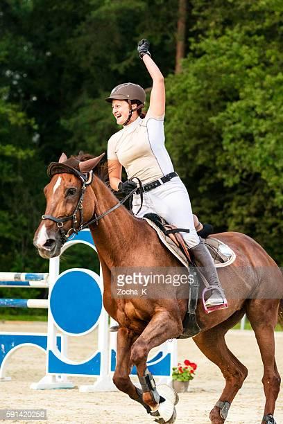 Female rider celebrates winning holding up hand
