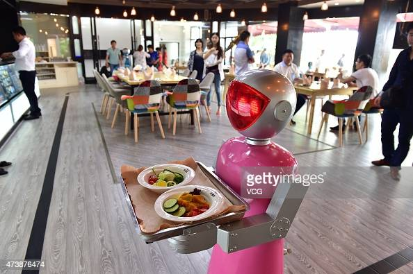 A 'female' robot waiter delivers meals for customers at robotthemed restaurant on May 18 2015 in Yiwu Zhejiang province of China Sophomore Xu Jinjin...