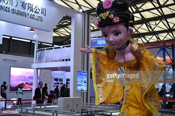 A female robot with big breasts in ancient costume twists on a booth during the CeMAT Asia 2015 at Shanghai New International Expo Centre on October...