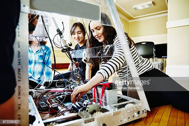 Female robotics team working on wiring of robot
