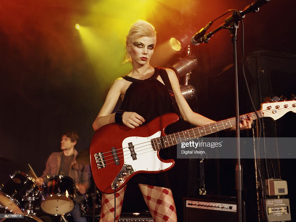 Female Rock Band Singer With Exaggerated Eye Make-up and a Blond Quiff Stands on Stage With an Electric Guitar, Drummer in the Background : Stock Photo