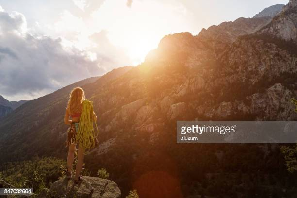 Female rock climber in the mountains at sunset