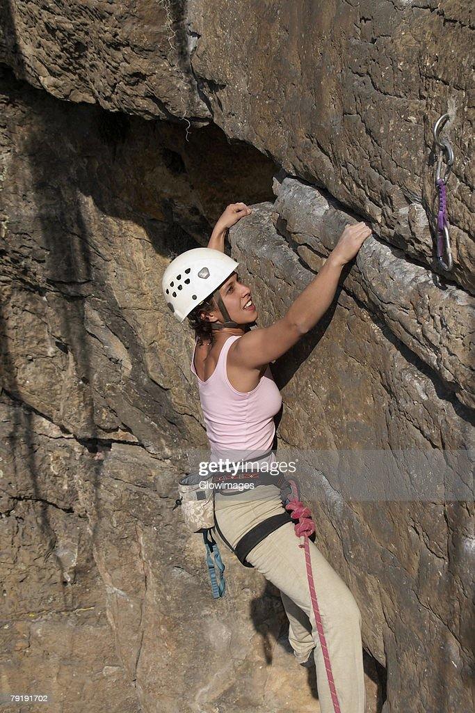 Female rock climber scaling a rock face : Foto de stock