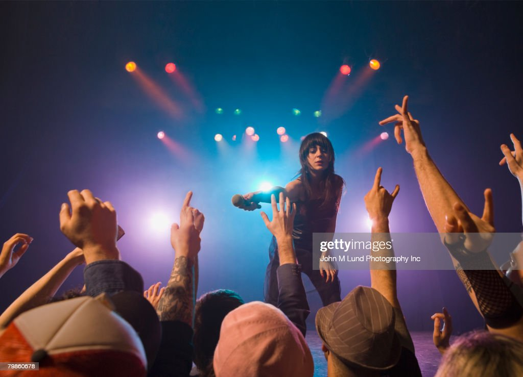 Female rock star on stage interacting with audience : Stock Photo