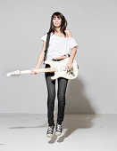 Female rocker looking cool jumping holding her guitar