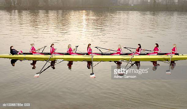 Female rowers rowing scull, side view