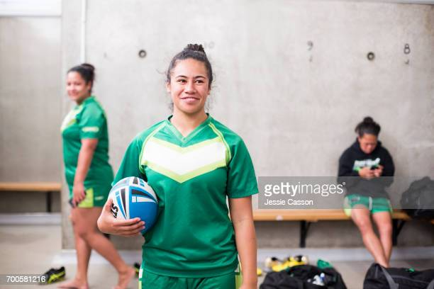 Female rugby player in changing rooms holding ball
