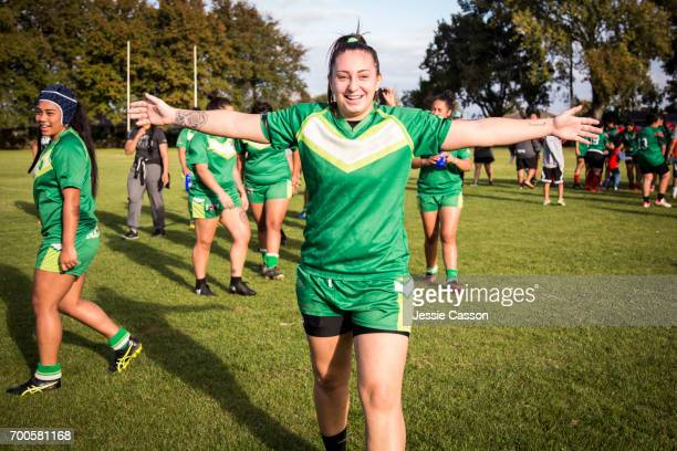 Female rugby player on field celebrating with arms stretched out