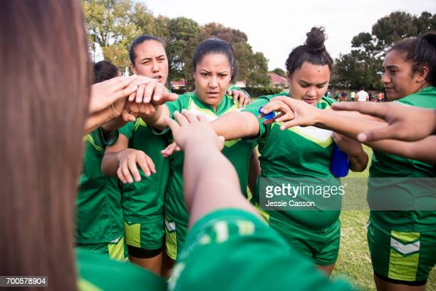 Female rugby players bonding in circle with hands together before game