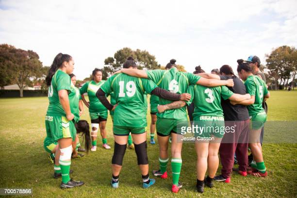 Female rugby players have team talk at side of pitch
