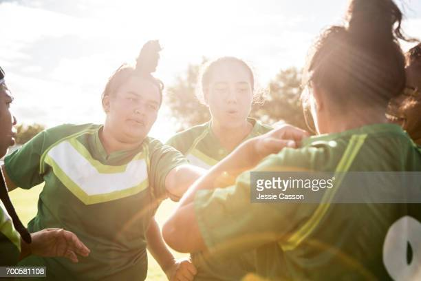 Female rugby players have team talk on field