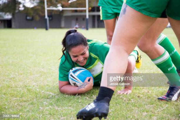 Female rugby players in action, one player in sliding on ground with ball smiling