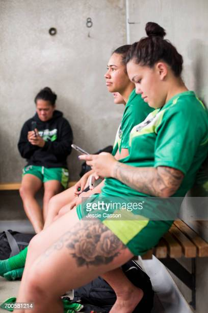 Female rugby players sitting on bench in changing rooms looking at mobile phone