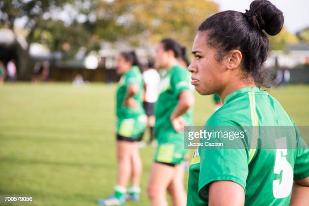 Female rugby players stand at edge of field watching match