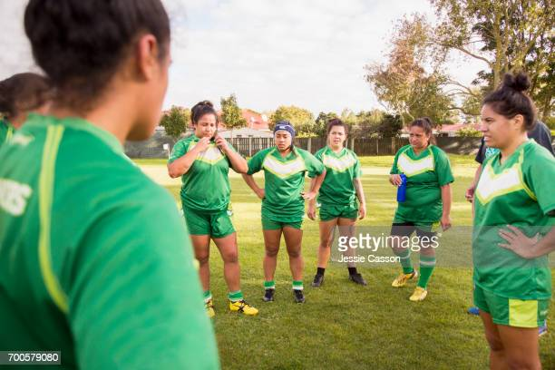 Female rugby players stand in circle having team talk at side of field