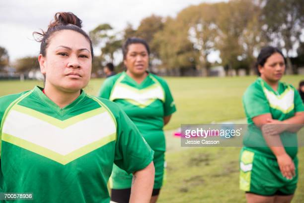 Female rugby players stand watching the game