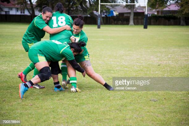 Female rugby players tackling in action
