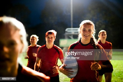 Female rugby team running together