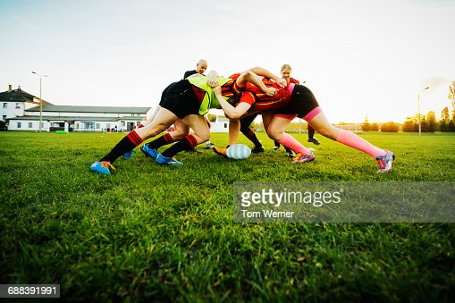 Female Rugby team training how to block