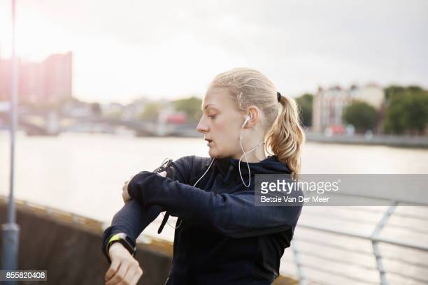 Female runner adjusting her mobile phone, getting ready to run.