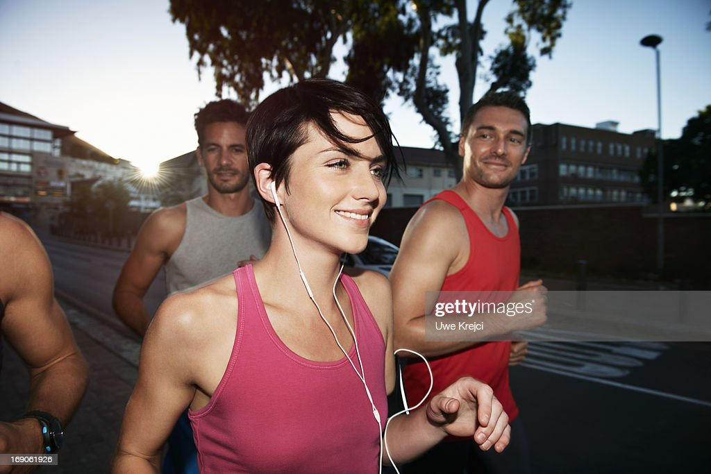 Female runner at evening run with friends : Stock Photo