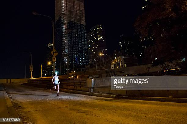 Female runner at night with city in the background