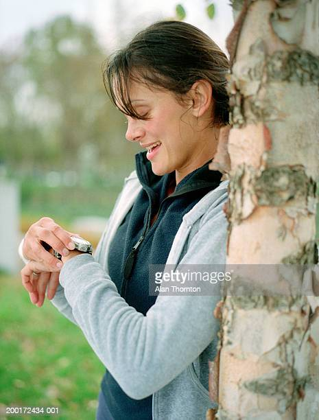 Female runner by tree checking watch, side view