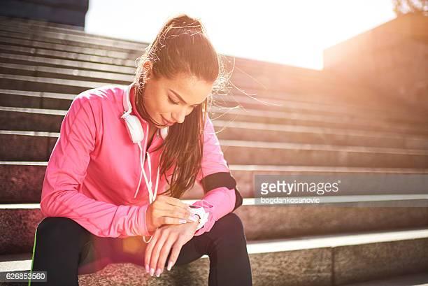 Mujer Corredor revisando información sobre reloj inteligente