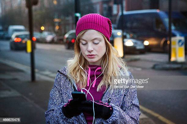 Female runner checking mobile phone on street.