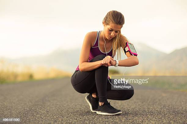 Female Runner Checking Time Along Road in Utah