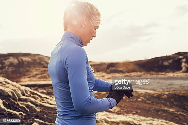 Female runner checks fitness tracker during run